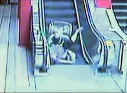 Guy falls down escalator in wheelchair